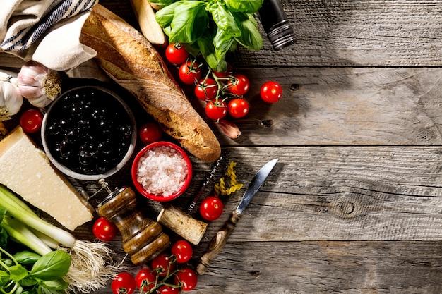 古い素朴な木製の背景に調理するためのおいしい食欲をそそるイタリア料理の材料。