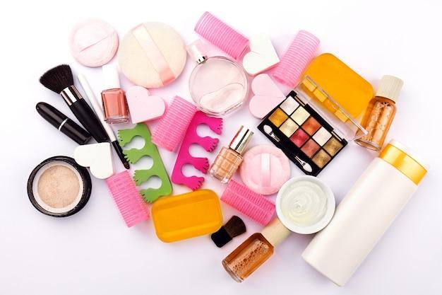 美容院フェミニンの概念。異なるメイクアップ美容ケアエッセンシャル化粧品フラットレイ白背景に。上面図。上。