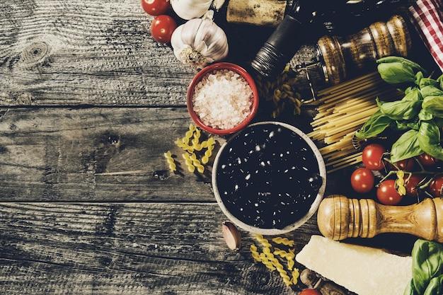 古いソーレッド木製の背景においしい食欲をそそるイタリア料理の成分。調理する準備ができました。ホームイタリアの健康食品調理の概念。トーニング