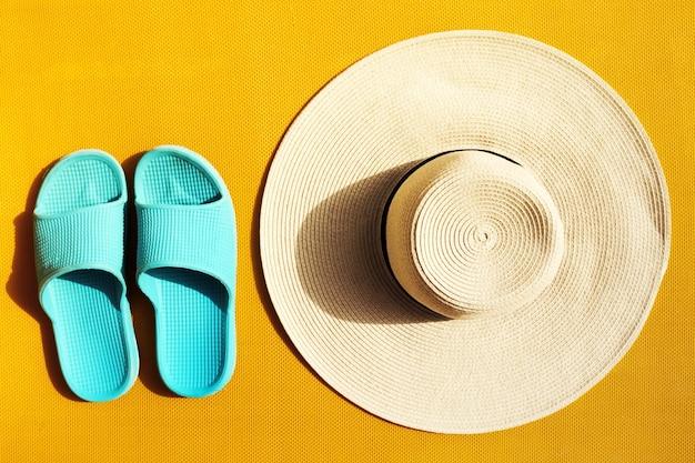 黄色い生き生きとした鮮やかな背景に青いフリップが付いている美しい麦わら帽子。上面図。フラットレイ。夏の旅行休暇の概念。
