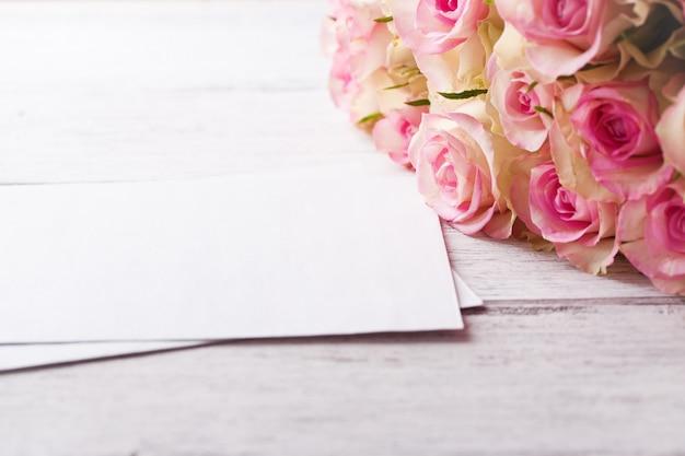 Букет из розовых роз с синей лентой на старинных деревянных фоне