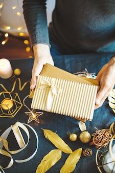 包まれた贈り物を示す人