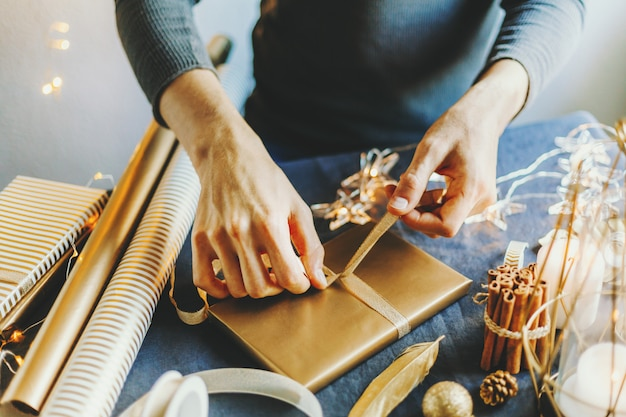 Человек делает лук из ленты на подарок