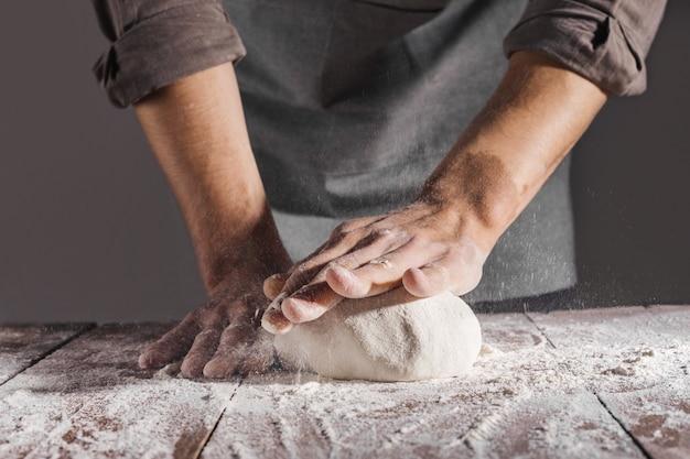 Шеф-повар делает и замешивает свежее тесто