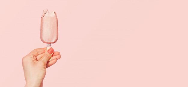 ピンクのアイスクリームを保持している若い女性