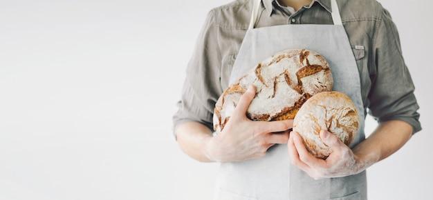 焼きたてのパンを保持しているパン屋さんやシェフ