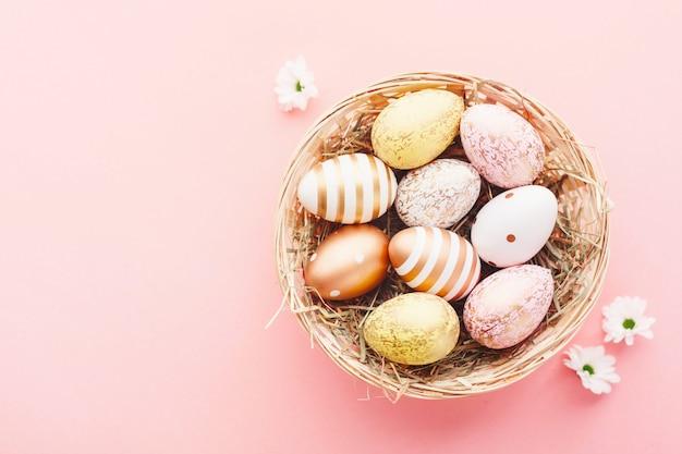 Пасхальная корзинка яиц в гнезде на розовом