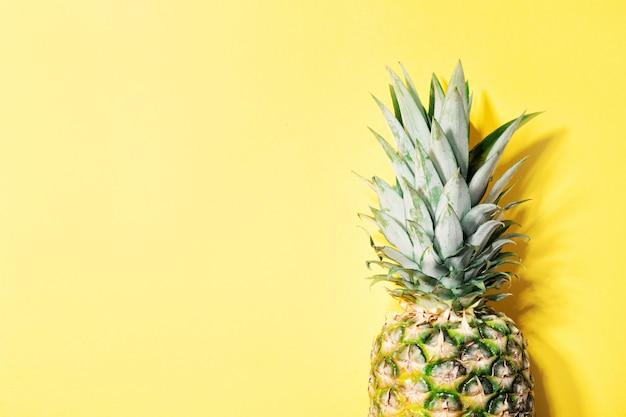 黄色の色の背景にパイナップル