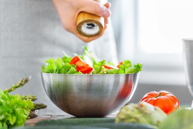 健康的なサラダを調理する若い男シェフ