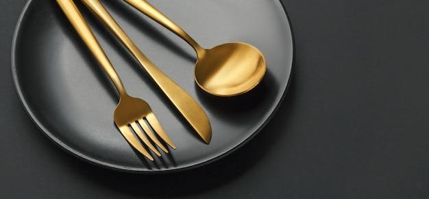 Набор золотых столовых приборов на черном фоне