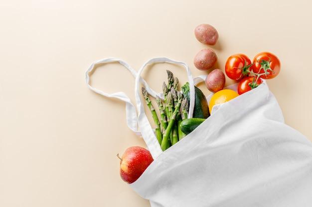 Разные овощи в текстильной сумке на бежевом