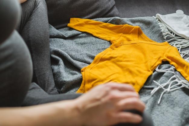 若い女性の赤ちゃんのための服を準備する