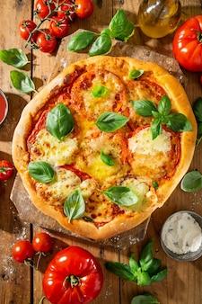 木製の背景にモッツァレラチーズと自家製ピザ