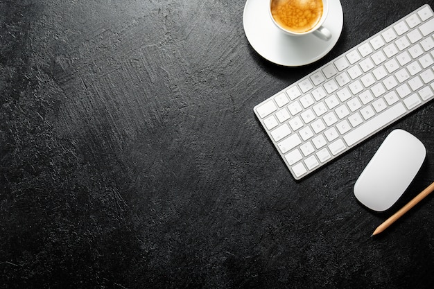 一杯のコーヒー、キーボード、メモ帳とオフィスのテーブル
