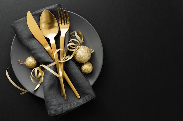 クリスマスディナーのプレートに金カトラリー