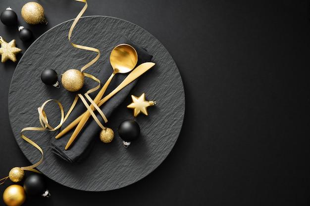 Золотые столовые приборы подаются на тарелку на рождественский ужин