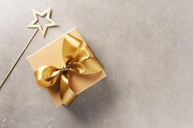 Подарочная коробка с золотой лентой на сером