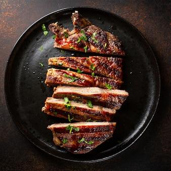 Стейк из говядины на гриле подается на тарелке