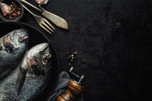 Рыба дорадо с ингредиентами на темном