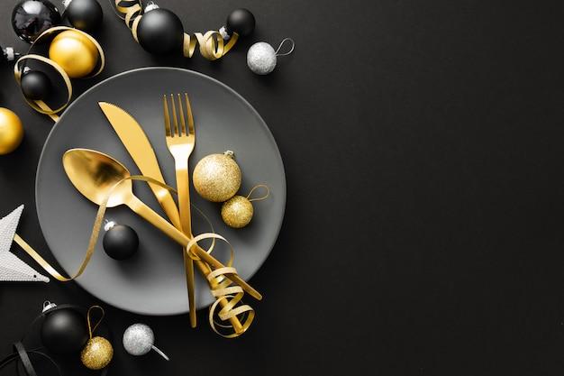 クリスマスディナーのプレートに金カトラリーを提供