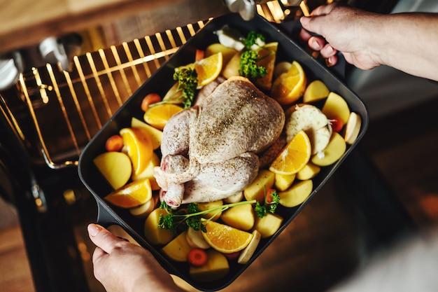 生野菜と鶏肉を調理する女性