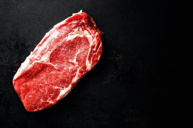 Сырой говяжий стейк на темной поверхности