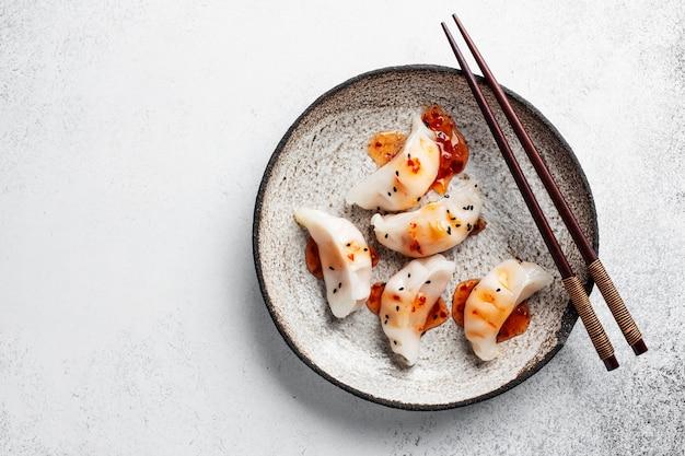 Азиатские пельмени подаются на тарелке
