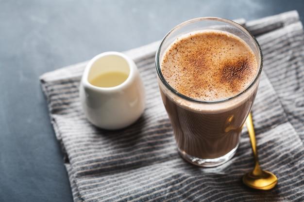 Чай латте в стакане с молоком