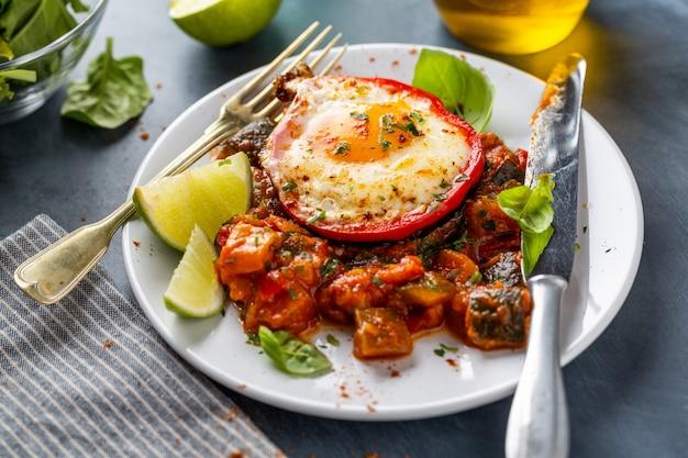 Жареное яйцо с овощами на тарелке