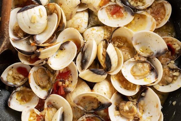 Вкусные аппетитные свежие домашние моллюски алле вонголе с чесноком и белым вином на сковороде. крупный план.