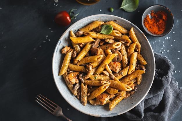 Вкусная аппетитная паста пенне с грибами в соусе. подается на тарелке.