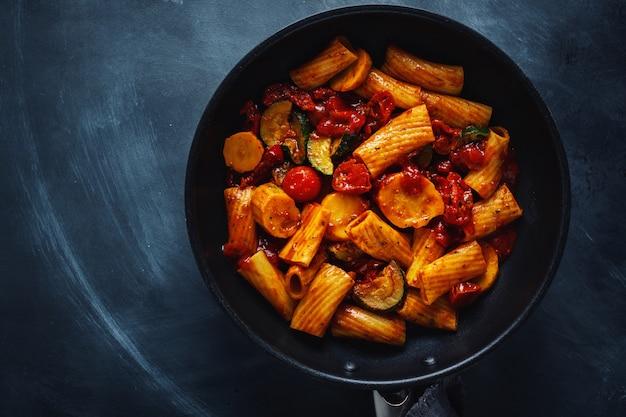 Вкусная аппетитная вегетарианская паста с овощами и томатным соусом подается на сковороде. вид сверху.