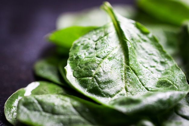 緑の葉は暗いテーブルの上にクローズアップ