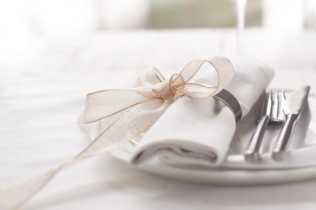 Тарелка с столовые приборы хорошо украшен салфеткой, привязанной с золотым бантом