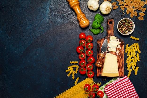 チーズ、パスタ、スパイスとまな板とトマト