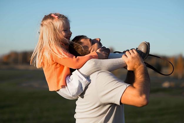С днем отца! девушка и папа ребенка играя на природе в поле лета