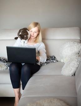 Зрелая женщина держит кота на плече и говорить через видео-чат
