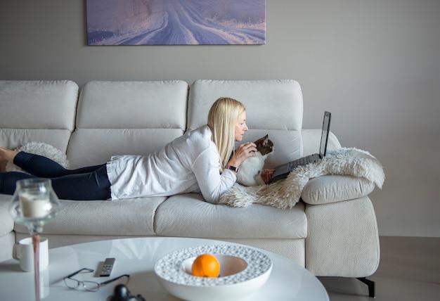 Зрелая женщина и милый кот разговаривают через видео-ч
