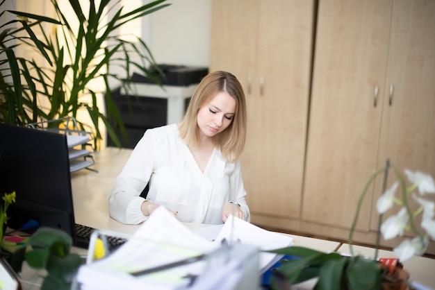 Деловая женщина, работающая в ее офисе
