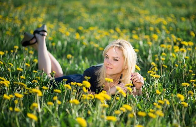 美しい若いブロンドの女性は夏の間に開花のタンポポの牧草地でリラックスします。