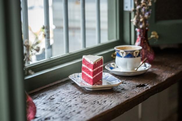 コーヒーマグカップタイの窓の近くでケーキ
