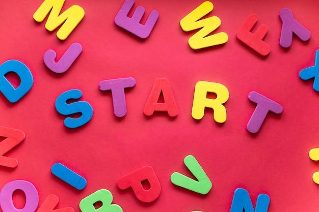 Слово старт из пластиковых магнитных букв на красном фоне