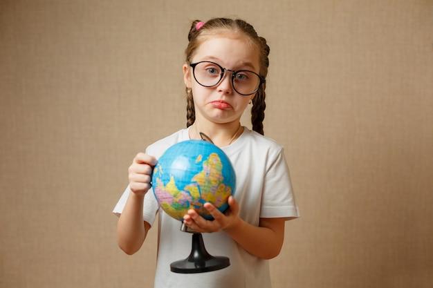 Красивая детская девочка в очках дома мечтает о путешествиях и туризме, изучает карту мира и земной шар