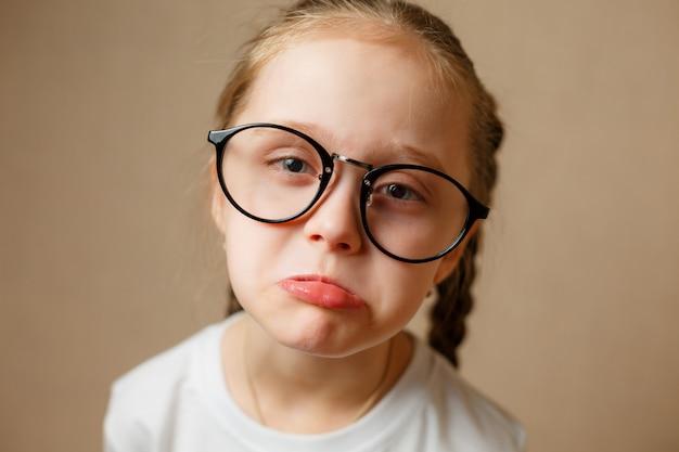 Грустная маленькая девочка в очках с серьезным лицом смотрит на верблюда