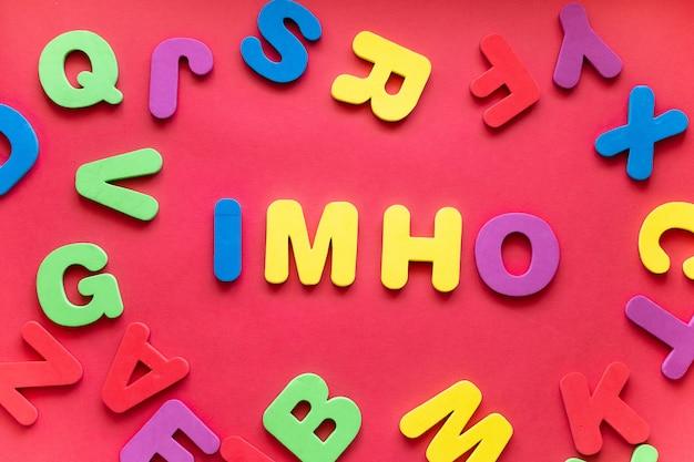 Аббревиатура имхо из пластиковых магнитных букв на красном фоне
