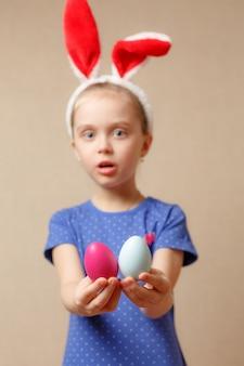 Милая усмехаясь маленькая девочка с красочными пасхальными яйцами. хв. выборочный фокус