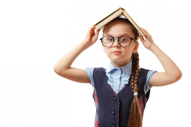 少女が彼女の頭に本を持っています