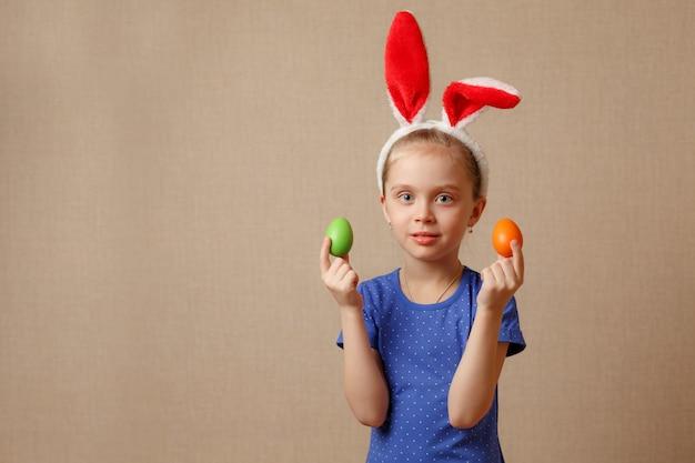 Милая усмехаясь маленькая девочка с красочными пасхальными яйцами. хв