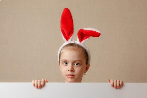Симпатичная маленькая девочка ищет из-за пустого баннера, в который можно вставить любой текст.