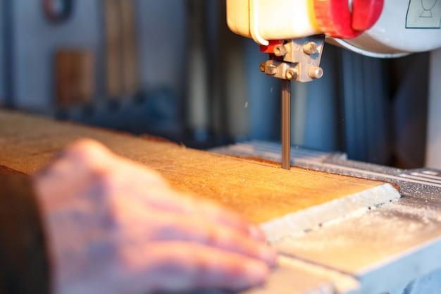 Карпентер резает кусок дерева с ленточной пилой в мастерской